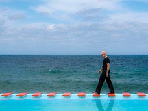 black-clad man walking across red stepping-blocks at the end of an infinity-edge pool facing the Straits of Florida in Havana