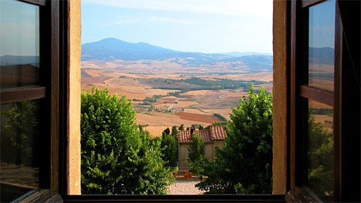 view of the Val d'Orcia through open casement window of inn in Pienza, Italy
