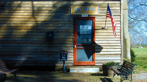 front door with benches to either side and flag flying from wood-frame wall beside door at Mooresville, Alabama post office, which is the oldest continuously operating post office in the state of Alabama