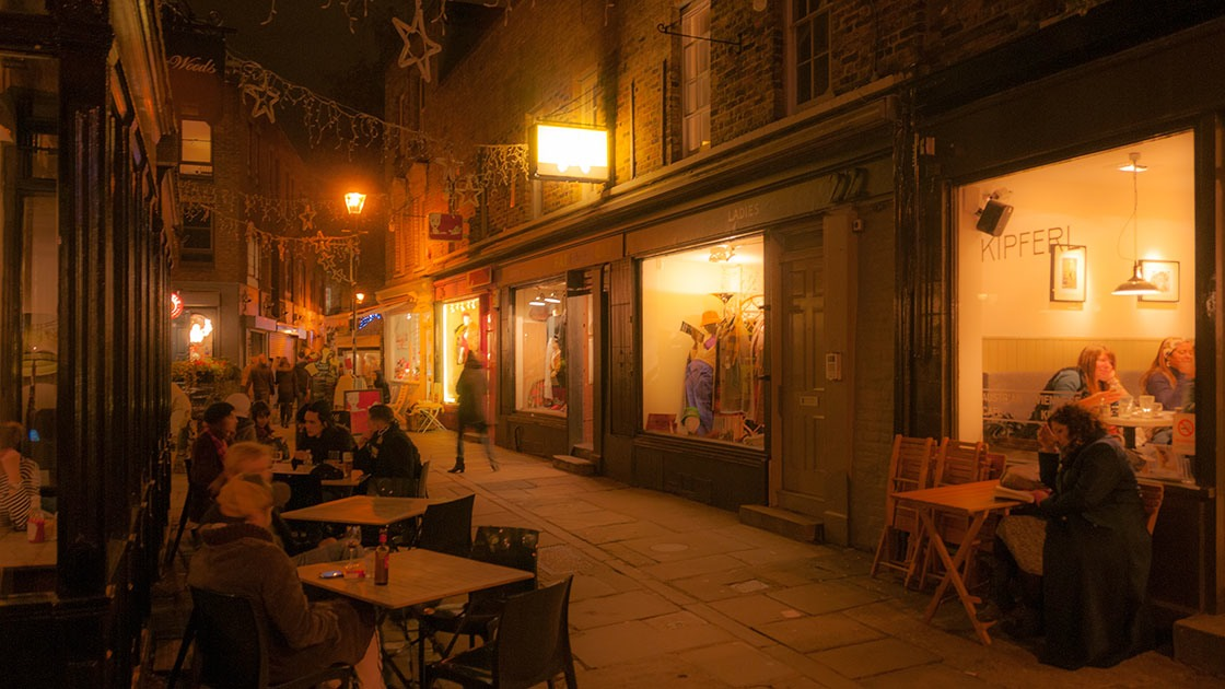 diners sitting at night along pedestrian street in London's Islington neighborhood, light spilling generously all around them from broad surrounding storefronts