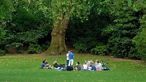 group of people sitting in a circle in a park in London