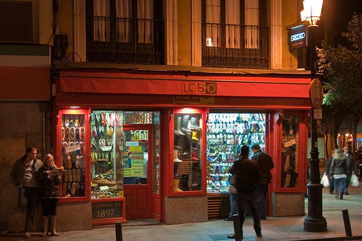 two shoppers peer through red-framed Madrid shopfront window under the watchful warm glow of an iron street lamp while another couple lounges against the wall where the shadows begin