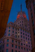clock with red glowing numerals and hands against early evening sky atop an office tower in Madrid, Spain