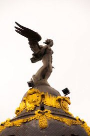 female winged figure sculpture atop building in Madrid, Spain