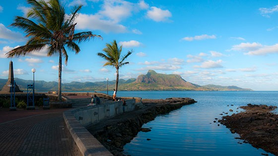 Mahebourg, Mauritius waterfront with monument and mountains across the sea