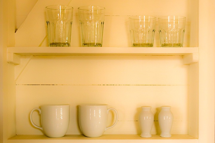 cups and glasses sit on shelves carved into white-painted cottage wall at Mahogany Bay Village on Ambergris Caye in Belize