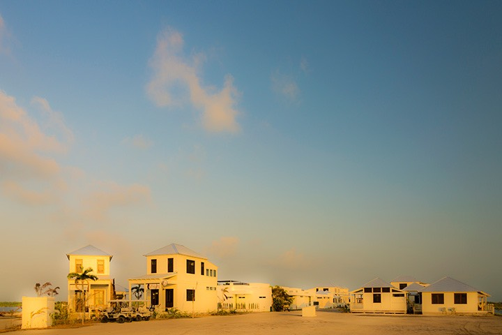 whitewashed shops and cottages of Mahogany Bay Village glow warm in the Belize sunrise on Ambergris Caye