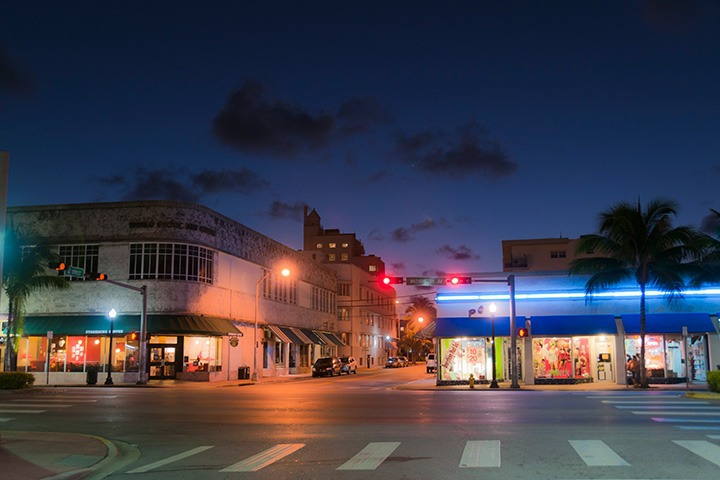 intersection of Washington Avenue and 12th Street in Miami Beach, with faint glow of receding sunset painting a gradient of blue across the sky as night draws on and the street lights glow
