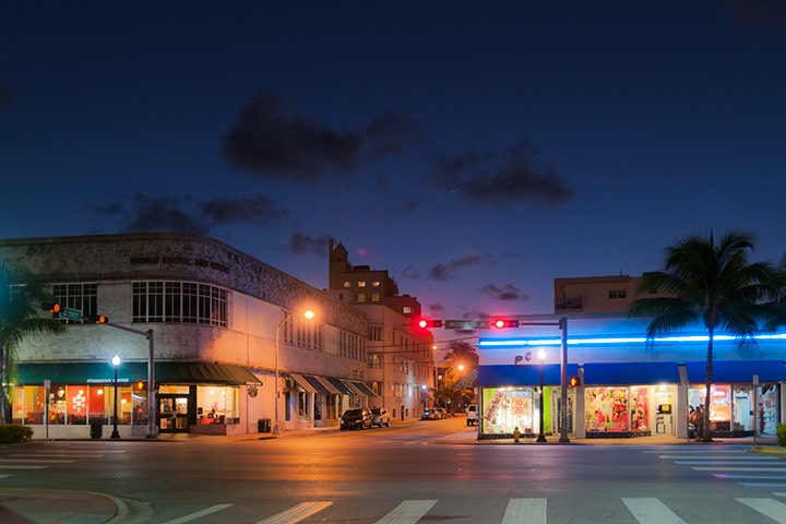 streetlights still glowing down on 12th Street on South Beach as it crosses Washington Avenue as dawn's early light begins to paint the nearly cloudless tropical sky