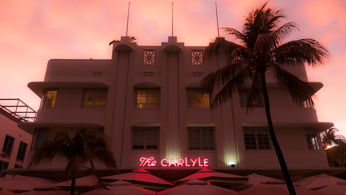 The Carlyle on South Beach glows a shaded pink against eerie glow of sunset-lit clouds.
