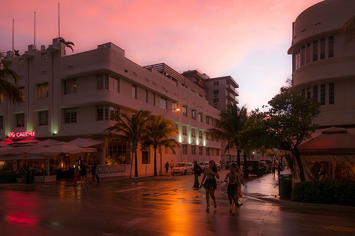 two girls crossing Ocean Drive in front of the Carlyle against neon and streetlight glow on glistening streets against backdrop of receding storm painting skies pink and French Blue on South Beach