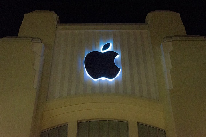 Apple Logo stands backlit with cool blue-white neon against the corrugated concrete battlements of the Apple Store on Miami Beach's Lincoln Road, all set against the inky night sky