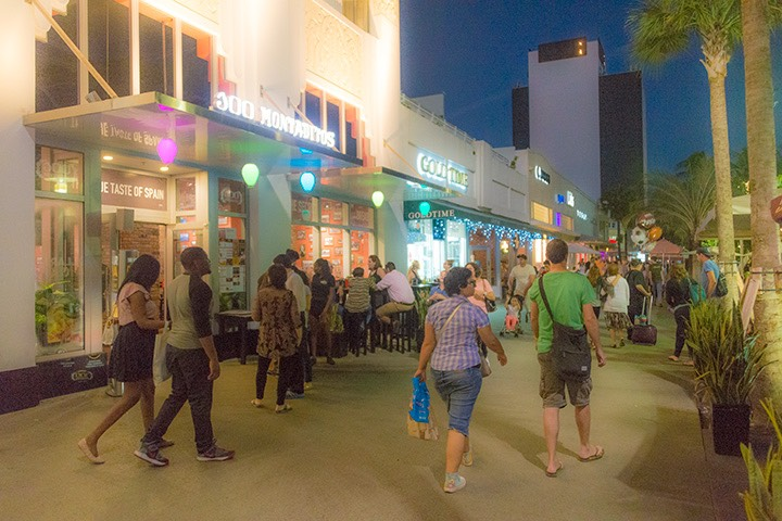 Miami Beach tourists walking along Lincoln Road as twilight descends beyond brightly-lit storefronts