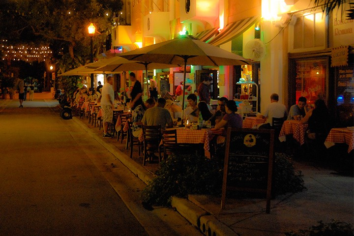 canvas umbrellas stand guard over their dinner guests as Española Way glows on a tropical South Beach evening