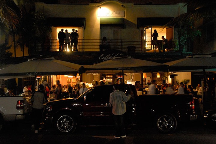 Young South Beach crowd packs sidewalk cafe and spills out onto balconies above as traffic snakes by at a crawl