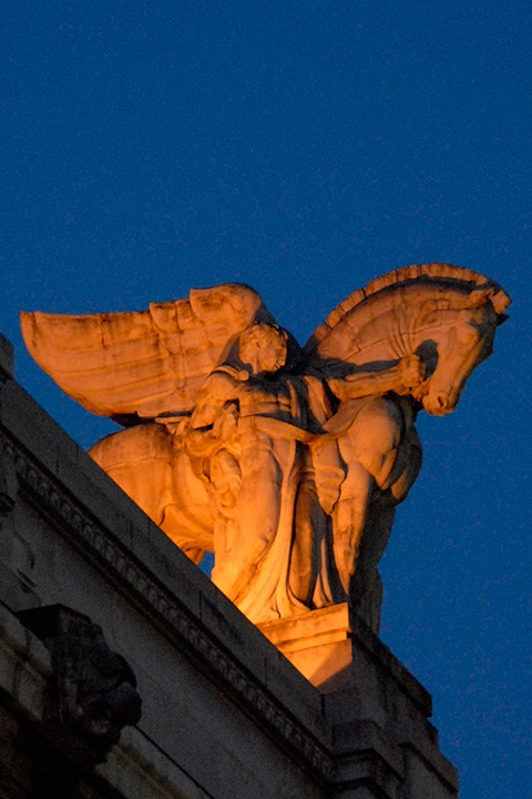 statue of man and horse atop a building in Milan bathed in orange light against the deepening blue of the evening sky