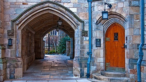 arched passage to left of brass-studded wooden arched door flanked by downspouts at Yale University