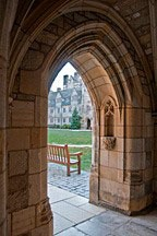 view through stone archway to bench looking into academic courtyard at Yale University