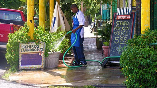 restaurant worker watering plants outside Schiro's in the Marigny Faubourg in New Orleans