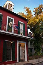 red stucco town house in the French Quarter of New Orleans with American flag and skull on second level balcony