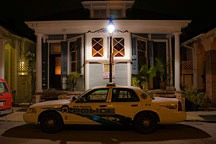 police car sitting on street at night in front of New Orleans double shotgun cottage