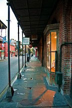 light spilling out of storefront bay window just after dawn in New Orleans