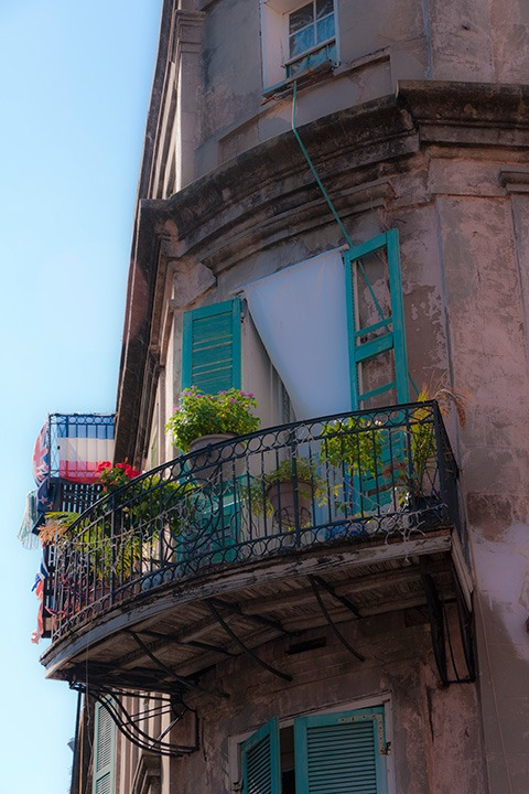 New Orleans French Quarter corner balcony bathed in early morning light, with breeze off the river folding white curtain into teal-shuttered opening