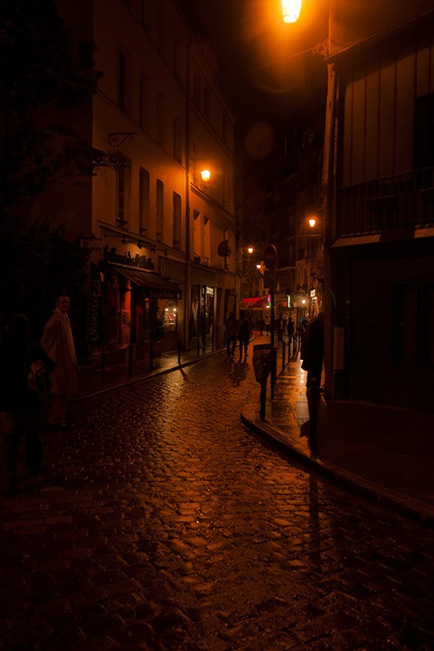 dark Paris cobbled street glistens under the orange glow of occasional street lamps