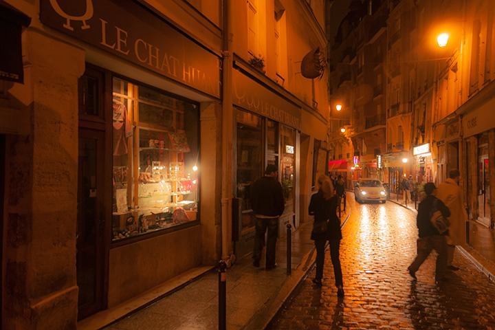 two people diverge along a narrow Paris cobbled street as a car approaches