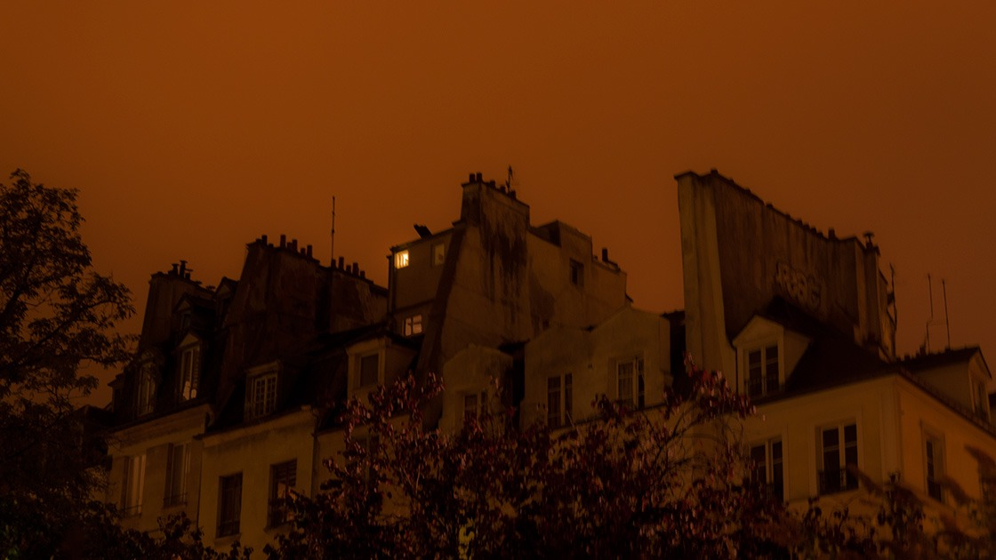 one lit attic window overlooks a Paris street as the city skyline leans heavily against the glowing Halloween underbelly of a cloudy night sky