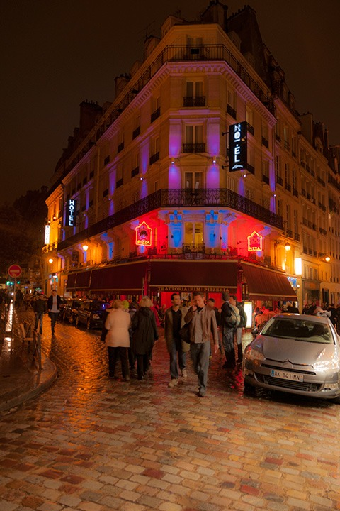neon-lit Paris flatiron building serves as backdrop for young men walking across glistening cobblestones after a rain