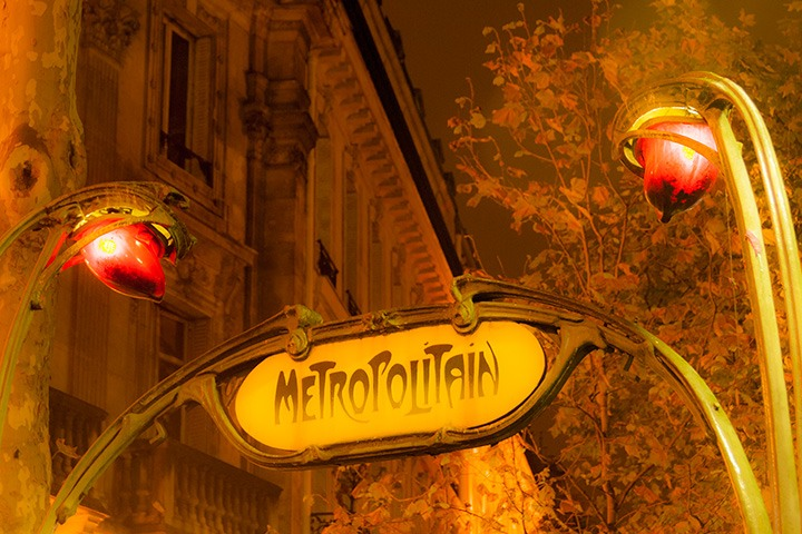 classic art nouveau sign lights entrance to Paris metro, framing a view to stone apartments lining the street beyond