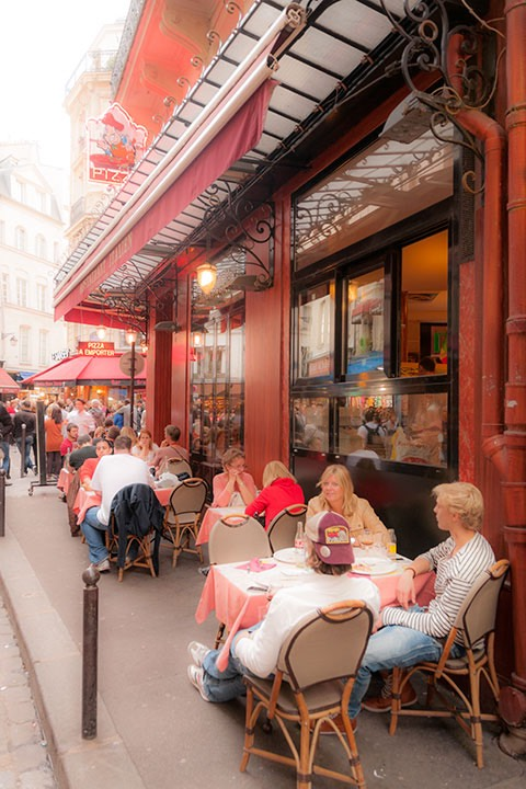 cast iron bollard protects diners at sidewalk cafe under wrought iron and glass awning set against salmon-hued restaurant in Paris