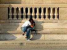 two lovers kissing on a bench at the Louvre in Paris