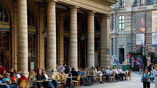 people sitting at a sidewalk cafe outside the Palais Royale in Paris