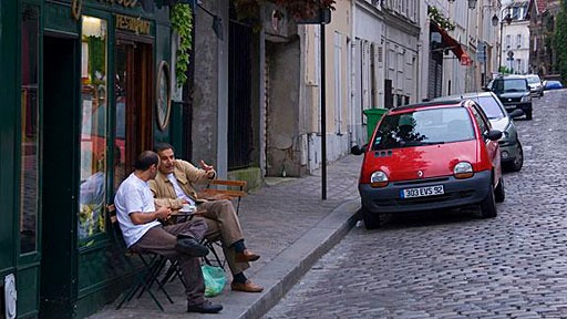 two men debating an issue at a table on the sidewalk outside a Paris cafe