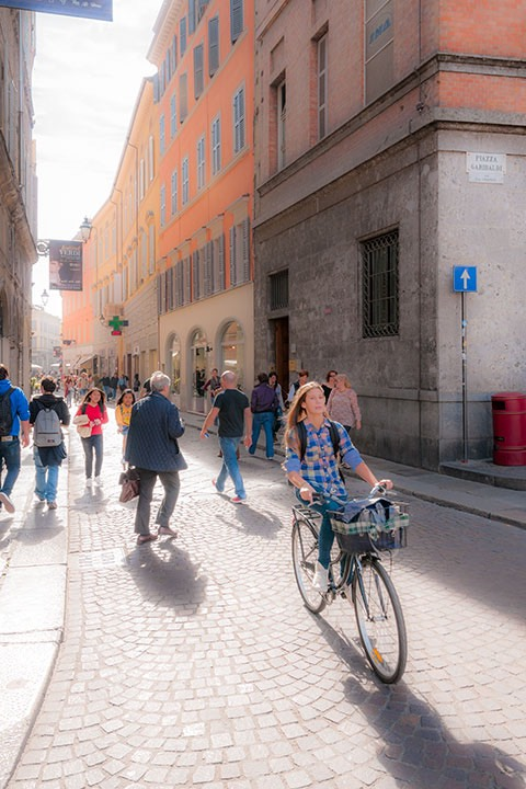 Parma street bends off into the midday sunshine, filled with people walking and biking to their daily needs