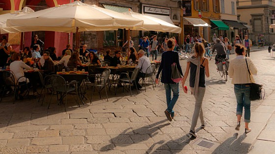 three women walking past a sidewalk cafe in Parma, Italy