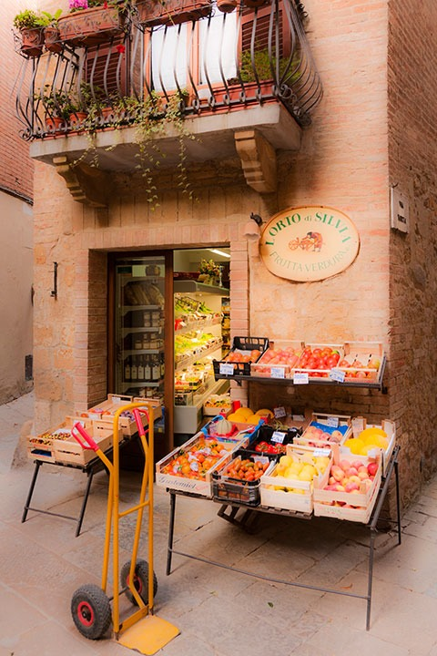 bright yellow hand truck sits outside a tiny Tuscan neighborhood market in Pienza, Italy as the vegetable deliveryman finalizes the transaction inside
