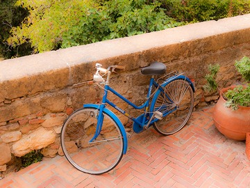 blue bicycle resting against stone wall in the soft Tuscan afternoon light of Pienza, Italy