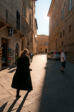 Wanda Mouzon walking through the streets of Pienza, Italy in early morning light