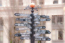 black pole with directional signs pointing to many cities and points of interest, located in Portland, Oregon