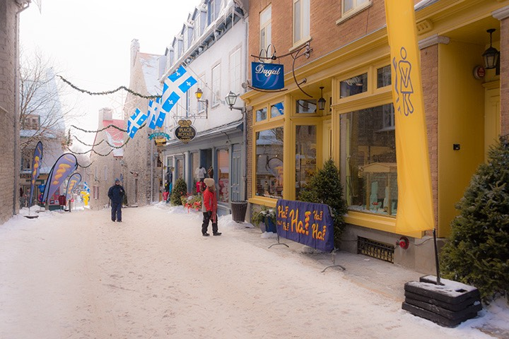 Quebec City shops sit upon a sidewalk coated with recently-fallen snow