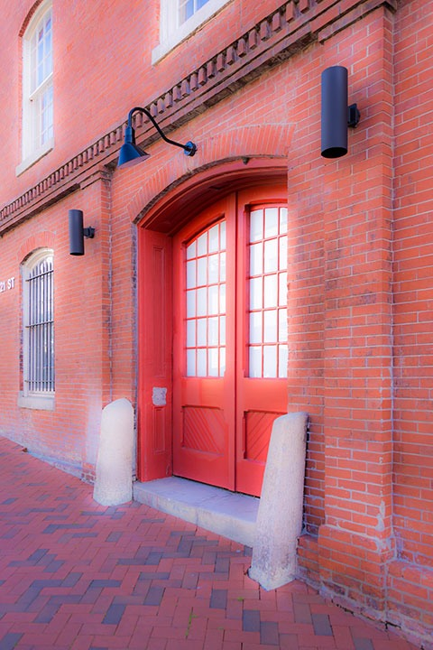 bright orange arched front doors set deep into a pilastered brick wall in Richmond's gritty Shockoe Bottom neighborhood