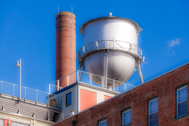 water tank and smokestack sprout in crisp winter morning light above the rooftops of brick loft buildings in Richmond's Shockoe Bottom