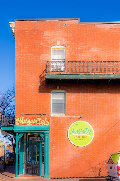 side brick wall of Shockoe Bottom margarita restaurant & bar gleams orange in the morning light of Richmond