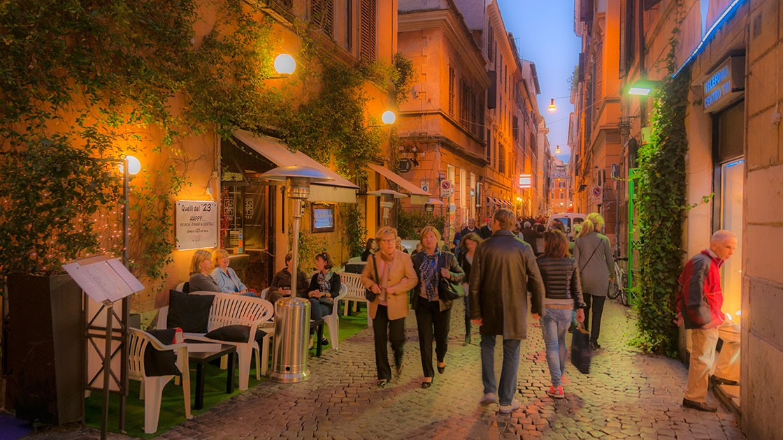 Rome street glows with streetlights in early evening, packed with people walking along the street and eating at sidewalk cafes that flank its edges