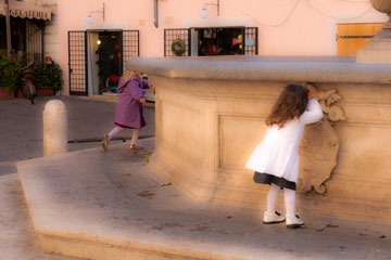 two little girls playing hide-and-seek in piazza in Rome