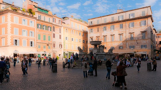 plaza in Rome with large fountain in center and 4-story stucco buildings all around