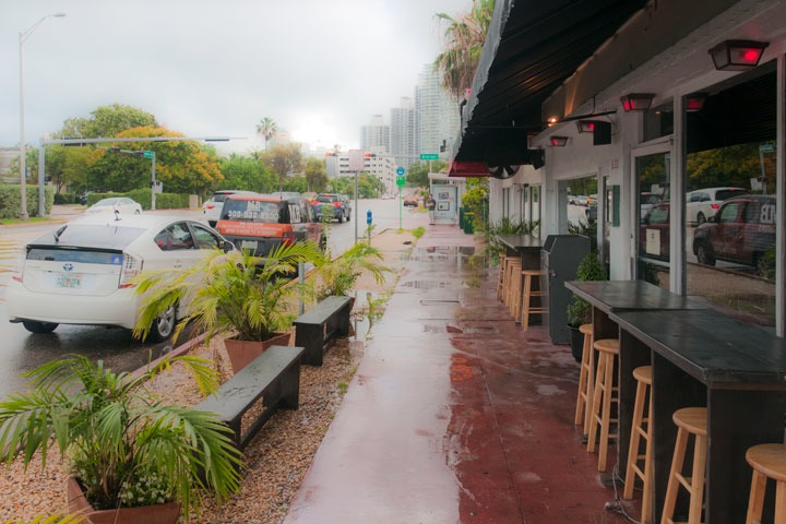 sidewalk cafe on Alton Road protected by parked cars on street